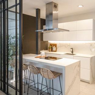 Foto de cocina de galera, contemporánea, cerrada, con fregadero bajoencimera, armarios con paneles lisos, puertas de armario blancas, una isla, suelo beige y encimeras blancas