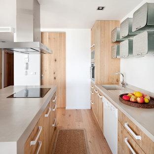 Imagen de cocina marinera con fregadero integrado, armarios con paneles lisos, puertas de armario de madera clara, suelo de madera clara, una isla y suelo beige