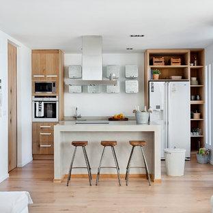 Modelo de cocina marinera, abierta, con armarios abiertos, puertas de armario de madera clara, salpicadero blanco, electrodomésticos blancos, suelo de madera clara, una isla y suelo beige