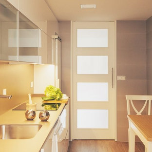 This is an example of a traditional single-wall separate kitchen in Other with an undermount sink, flat-panel cabinets, white cabinets, limestone benchtops, grey splashback, stone tile splashback, stainless steel appliances, porcelain floors, no island and brown floor.