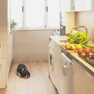 Photo of a traditional single-wall separate kitchen in Other with an undermount sink, flat-panel cabinets, white cabinets, limestone benchtops, grey splashback, stone tile splashback, stainless steel appliances, porcelain floors, no island and brown floor.