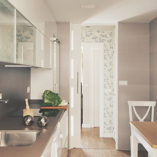 Traditional single-wall separate kitchen in Other with an undermount sink, flat-panel cabinets, white cabinets, limestone benchtops, grey splashback, stone tile splashback, stainless steel appliances, porcelain floors, no island and brown floor.