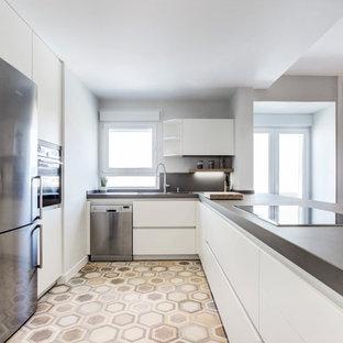 Modelo de cocina en U, nórdica, con electrodomésticos de acero inoxidable, encimeras grises, armarios con paneles lisos, puertas de armario blancas, encimera de cemento, salpicadero verde, suelo de azulejos de cemento, península y suelo beige