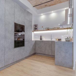 Ejemplo de cocina en L, industrial, sin isla, con armarios con paneles lisos, puertas de armario grises, electrodomésticos negros, suelo de madera clara y suelo beige
