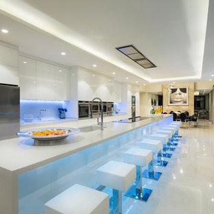 Diseño de cocina comedor actual, extra grande, con fregadero bajoencimera, armarios con paneles lisos, puertas de armario blancas, salpicadero blanco, electrodomésticos de acero inoxidable y una isla