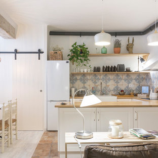 This is an example of a mid-sized country u-shaped open plan kitchen in Other with a farmhouse sink, raised-panel cabinets, white cabinets, wood benchtops, blue splashback, white appliances, terra-cotta floors, a peninsula and brown floor.