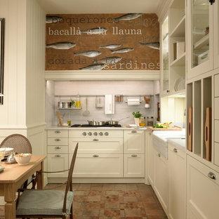Mid-sized midcentury kitchen in Barcelona with white cabinets, marble benchtops, white splashback, stone slab splashback, terra-cotta floors, recessed-panel cabinets and no island.