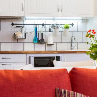 マラガの小さいコンテンポラリースタイルのおしゃれなキッチン (ドロップインシンク、フラットパネル扉のキャビネット、白いキャビネット、木材カウンター、白いキッチンパネル、セラミックタイルのキッチンパネル、白い調理設備、無垢フローリング、アイランドなし) の写真