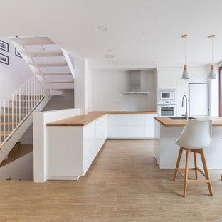 Foto de cocina en L, escandinava, con fregadero de un seno, armarios con paneles lisos, puertas de armario blancas, encimera de madera, electrodomésticos blancos, suelo de madera clara, una isla y suelo beige