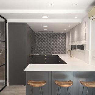 Diseño de cocina en U, clásica renovada, con fregadero integrado, armarios estilo shaker, puertas de armario grises, salpicadero blanco, península y encimeras blancas