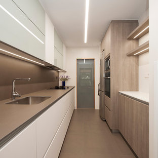 Design ideas for a mid-sized modern galley separate kitchen in Barcelona with a single-bowl sink, flat-panel cabinets, white cabinets, limestone benchtops, brown splashback, limestone splashback, black appliances, porcelain floors, no island and brown floor.