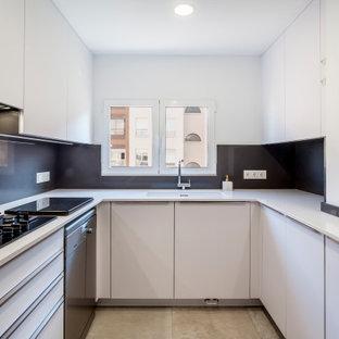Imagen de cocina en U, contemporánea, sin isla, con fregadero bajoencimera, armarios con paneles lisos, puertas de armario blancas, salpicadero negro, electrodomésticos de acero inoxidable, suelo gris y encimeras blancas