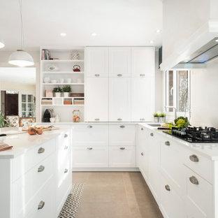 Diseño de cocina en L, contemporánea, de tamaño medio, cerrada, con fregadero bajoencimera, armarios estilo shaker, puertas de armario blancas, electrodomésticos con paneles, suelo de baldosas de porcelana, una isla, suelo beige y encimeras blancas