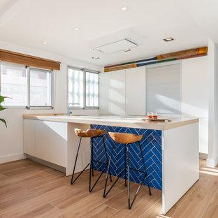 Ejemplo de cocina de galera, costera, de tamaño medio, abierta, con armarios con paneles lisos, puertas de armario blancas, electrodomésticos con paneles, península, suelo beige y encimeras beige