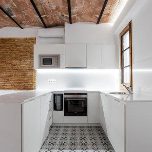 バルセロナの小さい地中海スタイルのおしゃれなキッチン (フラットパネル扉のキャビネット、白いキャビネット、白いキッチンパネル、シルバーの調理設備の、セラミックタイルの床、ドロップインシンク、グレーの床、白いキッチンカウンター) の写真