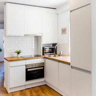 他の地域の小さい北欧スタイルのおしゃれなキッチン (アンダーカウンターシンク、フラットパネル扉のキャビネット、白いキャビネット、木材カウンター、白いキッチンパネル、セラミックタイルのキッチンパネル、シルバーの調理設備の、無垢フローリング、アイランドなし) の写真