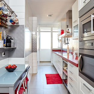 Mid-sized contemporary single-wall separate kitchen in Madrid with a double-bowl sink, raised-panel cabinets, white cabinets, quartz benchtops, grey splashback, ceramic splashback, stainless steel appliances, porcelain floors, no island, grey floor and red benchtop.