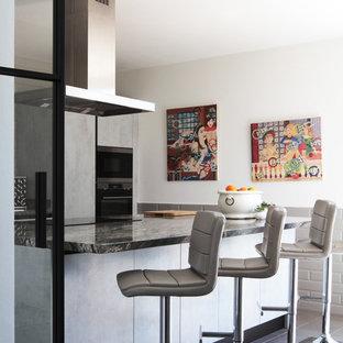 Diseño de cocina de galera, actual, con armarios con paneles lisos, puertas de armario grises, una isla, suelo negro y encimeras negras