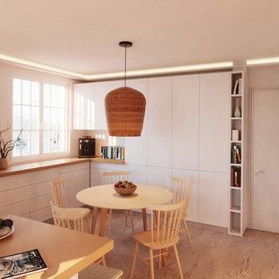 マドリードの中サイズの地中海スタイルのおしゃれなキッチン (一体型シンク、フラットパネル扉のキャビネット、白いキャビネット、木材カウンター、ガラスまたは窓のキッチンパネル、シルバーの調理設備の、無垢フローリング、茶色い床、茶色いキッチンカウンター) の写真