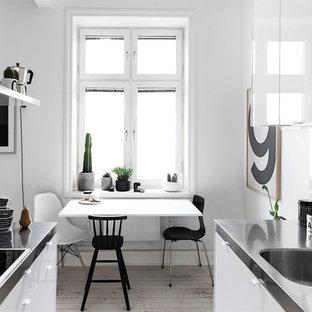 Modelo de cocina comedor en U, tradicional renovada, pequeña, sin isla, con fregadero de un seno, armarios con paneles lisos, puertas de armario blancas, salpicadero blanco, suelo de madera en tonos medios y encimera de acero inoxidable