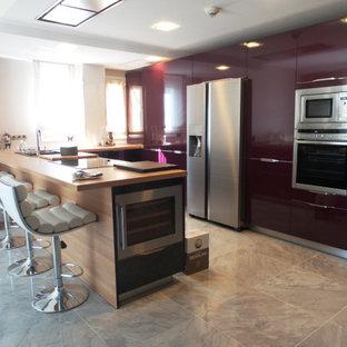 Modern inredning av ett stort brun brunt kök, med en rustik diskho, släta luckor, lila skåp, träbänkskiva, rostfria vitvaror, marmorgolv, en köksö och vitt golv