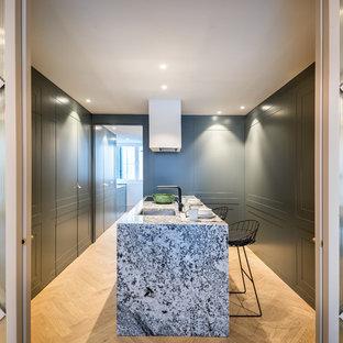 Ejemplo de cocina en U, contemporánea, cerrada, con fregadero bajoencimera, puertas de armario verdes, suelo de madera en tonos medios, una isla, suelo marrón y encimeras multicolor
