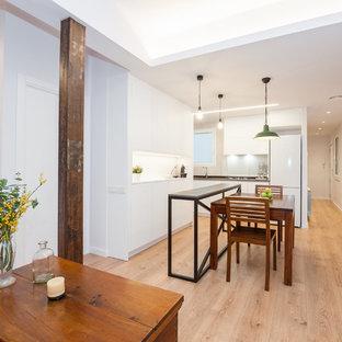 Modelo de cocina actual, grande, abierta, con armarios con paneles lisos, puertas de armario blancas, salpicadero blanco, una isla, encimeras negras, suelo de madera clara y suelo beige