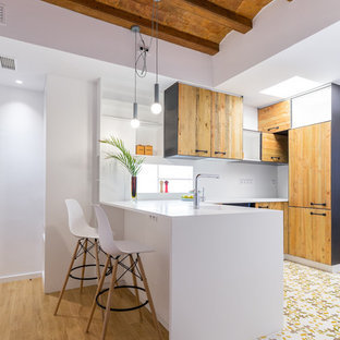 Design ideas for a mid-sized mediterranean u-shaped kitchen in Barcelona with a single-bowl sink, medium wood cabinets, solid surface benchtops, white splashback, ceramic floors, white benchtop, flat-panel cabinets, a peninsula and multi-coloured floor.