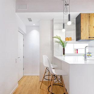 Imagen de cocina moderna, cerrada, con fregadero integrado, armarios con paneles lisos, puertas de armario blancas, suelo de madera clara, península, suelo beige y encimeras blancas