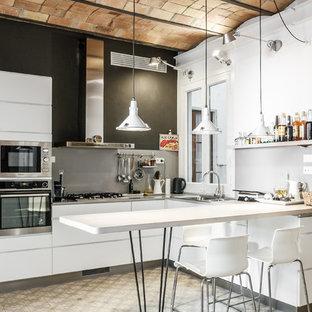 Imagen de cocina en L, urbana, de tamaño medio, con armarios con paneles lisos, puertas de armario blancas, salpicadero verde, suelo de baldosas de cerámica, península y electrodomésticos de acero inoxidable