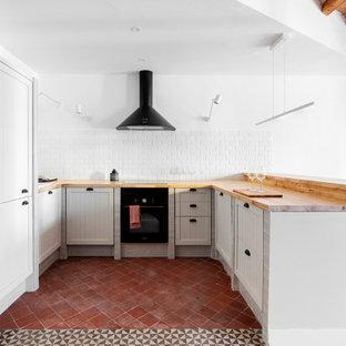 バルセロナの地中海スタイルのおしゃれなキッチン (ドロップインシンク、シェーカースタイル扉のキャビネット、グレーのキャビネット、木材カウンター、白いキッチンパネル、サブウェイタイルのキッチンパネル、黒い調理設備、赤い床、茶色いキッチンカウンター) の写真
