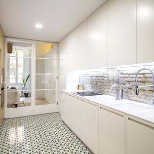 Modelo de cocina lineal, actual, de tamaño medio, cerrada, sin isla, con fregadero de doble seno, armarios con paneles lisos, puertas de armario blancas, electrodomésticos con paneles, suelo de baldosas de cerámica y encimeras blancas
