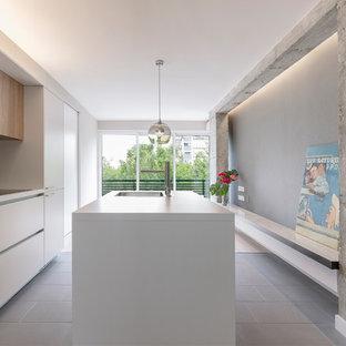 Ejemplo de cocina de galera, actual, con fregadero encastrado, armarios con paneles lisos, puertas de armario blancas, salpicadero verde, electrodomésticos con paneles, una isla, suelo gris y encimeras blancas