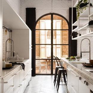 Zweizeilige, Große Shabby-Chic-Style Wohnküche ohne Insel mit flächenbündigen Schrankfronten, weißen Schränken, Küchenrückwand in Weiß, Rückwand aus Zementfliesen und gebeiztem Holzboden in Sonstige