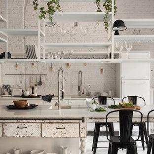 Cette image montre une grande cuisine américaine parallèle style shabby chic avec un évier 1 bac, un placard sans porte, des portes de placard blanches, un sol en bois peint et un îlot central.