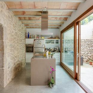 Imagen de cocina lineal, mediterránea, pequeña, abierta, con armarios con paneles lisos, puertas de armario blancas, salpicadero blanco, electrodomésticos de acero inoxidable, suelo de cemento y una isla