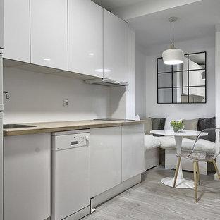 Modelo de cocina comedor lineal, escandinava, sin isla, con fregadero encastrado, armarios con paneles lisos, puertas de armario blancas, encimera de madera, salpicadero blanco, electrodomésticos blancos, suelo gris, encimeras beige y suelo de madera clara