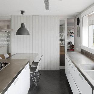 Immagine di una grande cucina parallela nordica chiusa con lavello a doppia vasca, ante lisce, ante bianche, top in acciaio inossidabile, elettrodomestici in acciaio inossidabile, pavimento in cemento, isola e top grigio