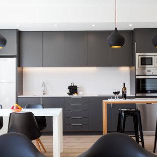 Diseño de cocina lineal, contemporánea, de tamaño medio, abierta, con armarios con paneles lisos, salpicadero blanco, electrodomésticos de acero inoxidable, suelo de madera en tonos medios, península, puertas de armario negras y suelo marrón