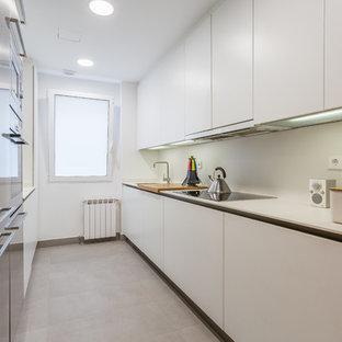 Ejemplo de cocina de galera, contemporánea, de tamaño medio, cerrada, sin isla, con armarios con paneles lisos, puertas de armario blancas, salpicadero blanco, encimeras blancas, fregadero bajoencimera y suelo gris