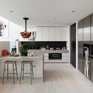 Idéer för ett stort klassiskt grå kök, med släta luckor, vita skåp, rostfria vitvaror, ljust trägolv, svart stänkskydd och en halv köksö