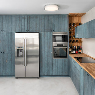 Mid-sized contemporary l-shaped kitchen in Other with an undermount sink, louvered cabinets, turquoise cabinets, wood benchtops, stainless steel appliances, no island, grey floor and beige benchtop.