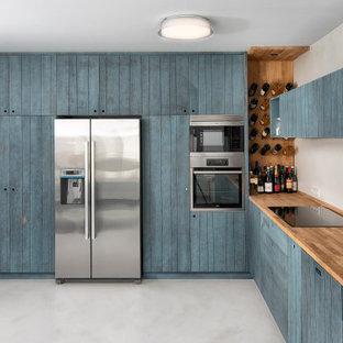 Modelo de cocina en L, actual, de tamaño medio, sin isla, con fregadero bajoencimera, armarios con puertas mallorquinas, puertas de armario turquesas, encimera de madera, electrodomésticos de acero inoxidable, suelo gris y encimeras beige
