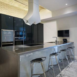 Imagen de cocina lineal, minimalista, grande, cerrada, con fregadero de un seno, armarios con paneles lisos, puertas de armario negras, encimera de zinc, electrodomésticos negros, suelo de baldosas de porcelana, una isla y suelo gris