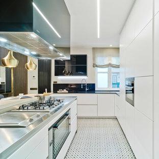 Diseño de cocina en L, actual, abierta, con armarios con paneles lisos, puertas de armario blancas, encimera de acero inoxidable, una isla, fregadero bajoencimera, electrodomésticos de acero inoxidable, suelo multicolor y encimeras grises
