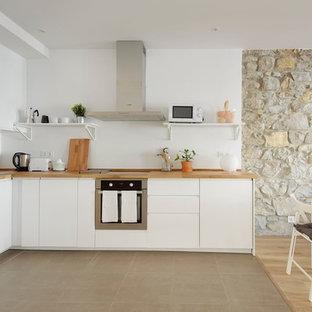 Ejemplo de cocina en L, mediterránea, abierta, sin isla, con fregadero encastrado, armarios con paneles lisos, puertas de armario blancas, encimera de madera, salpicadero blanco, suelo gris y encimeras beige