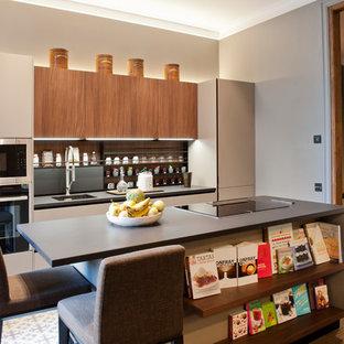 Diseño de cocina de galera, contemporánea, de tamaño medio, abierta, con fregadero bajoencimera, armarios con paneles lisos, puertas de armario grises, salpicadero marrón, salpicadero de madera, electrodomésticos negros, una isla y suelo multicolor