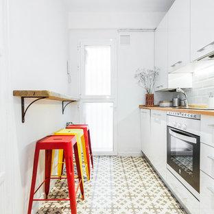 マドリードの小さい北欧スタイルのおしゃれなキッチン (シングルシンク、白いキャビネット、木材カウンター、白いキッチンパネル、サブウェイタイルのキッチンパネル、シルバーの調理設備の、セラミックタイルの床、アイランドなし) の写真