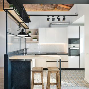 Enclosed kitchen - small industrial u-shaped light wood floor enclosed kitchen idea in Barcelona with flat-panel cabinets, white cabinets, white backsplash, subway tile backsplash, stainless steel appliances and a peninsula
