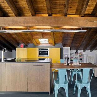 Foto de cocina de galera, actual, grande, con armarios con paneles lisos, una isla, suelo negro y puertas de armario amarillas